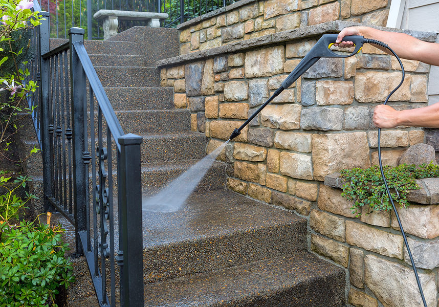 cleaner doing power washing stairs